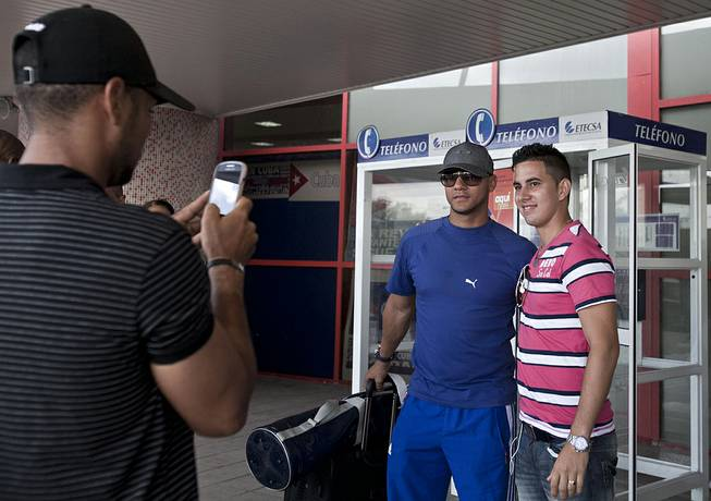 In this May 29, 2014 photo, Yulieski Gourriel, center, a player with Cuba's baseball team Industriales, poses for a photo with a fan before catching his flight at the Jose Marti International Airport, in Havana, Cuba. Gourriel signed a contract with the DeNA BayStars of Yokohama, Japan, for the next half-year.