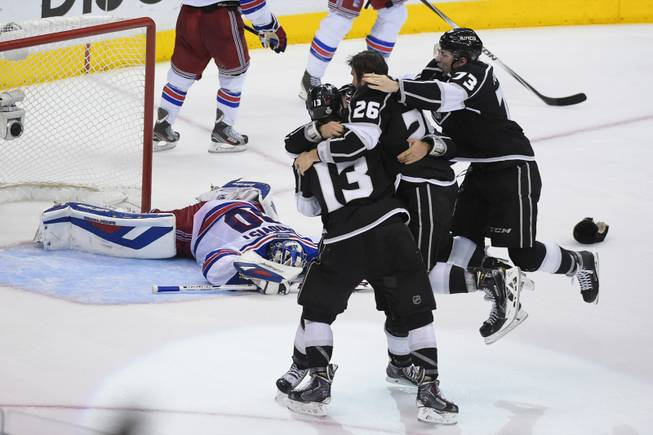 The Los Angeles Kings celebrate as New York Rangers goalie Henrik Lundqvist, of Sweden, lies on the ice behind, after the Kings beat the Rangers in double overtime in Game 5 of the NHL Stanley Cup Final series Friday, June 13, 2014, in Los Angeles. (AP Photo/Mark J. Terrill)