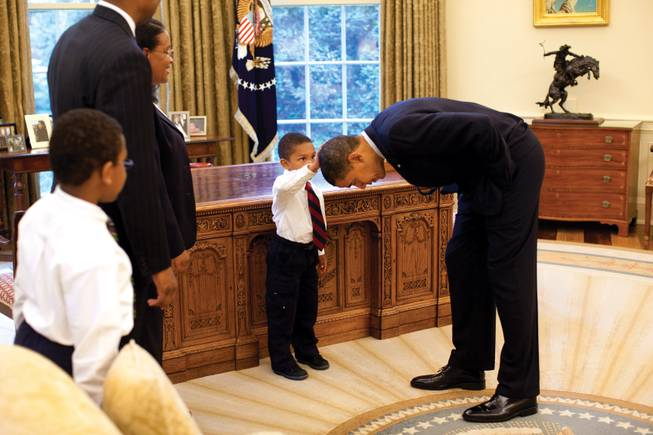 President Barack Obama bends over so the son of a White House staff member can feel his hair during a visit to the Oval Office on May 8, 2009.