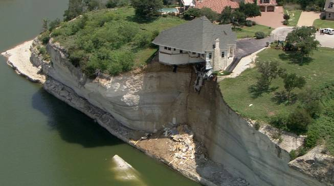 In this image taken from video provided Thursday, June 12, 2014, by WFAA.Com, a luxury house teeters on a cliff about 75 feet above Lake Whitney in Whitney, Texas.