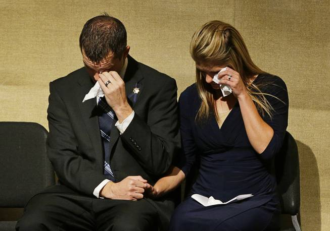 Joseph Beck, left, and Elizabeth Krmpotich wipe tears from their eyes during a memorial service for their brother Las Vegas Metropolitan Police Officer Alyn Beck at The Smith Center for the Performing Arts Saturday, June 14, 2014 in Las Vegas. Two suspects shot and killed Beck, 41, and fellow police officer Igor Soldo, 31, in an ambush at a Las Vegas restaurant Sunday, June 8, 2014, before fatally shooting a third person inside a nearby Wal-Mart, authorities said.