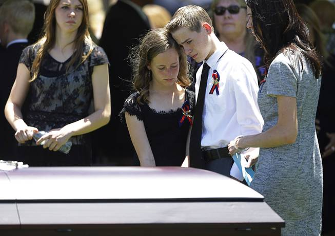 Daxton Beck, center right, leans his head on his sister Avenlee Beck as they stand over the casket of their father Las Vegas Metropolitan Police Officer Alyn Beck during a memorial at The Smith Center for the Performing Arts Saturday, June 14, 2014 in Las Vegas. Two suspects shot and killed Beck, 41, and fellow police officer Igor Soldo, 31, in an ambush at a Las Vegas restaurant Sunday, June 8, 2014, before fatally shooting a third person inside a nearby Wal-Mart, authorities said.