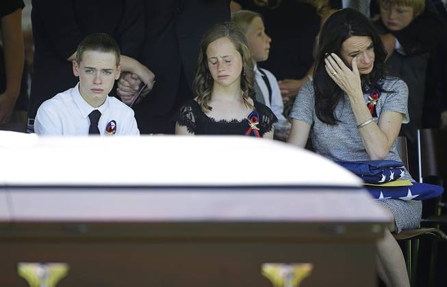 From left, Daxton Beck, Avenlee Beck and their mother Nicole Beck attend a memorial for Nicole Beck's husband Las Vegas Metropolitan Police Officer Alyn Beck at The Smith Center for the Performing Arts Saturday, June 14, 2014 in Las Vegas. Daxton and Avenlee are Alyn Beck's children. Two suspects shot and killed Beck, 41, and fellow police officer Igor Soldo, 31, in an ambush at a Las Vegas restaurant Sunday, June 8, 2014, before fatally shooting a third person inside a nearby Wal-Mart, authorities said.