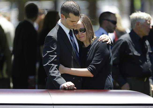 Joseph Beck, left, embraces an unidentified woman as they stand over the casket of Beck's brother Las Vegas Metropolitan Police Officer Alyn Beck during a memorial at The Smith Center for the Performing Arts Saturday, June 14, 2014 in Las Vegas. Two suspects shot and killed Beck, 41, and fellow police officer Igor Soldo, 31, in an ambush at a Las Vegas restaurant Sunday, June 8, 2014, before fatally shooting a third person inside a nearby Wal-Mart, authorities said.