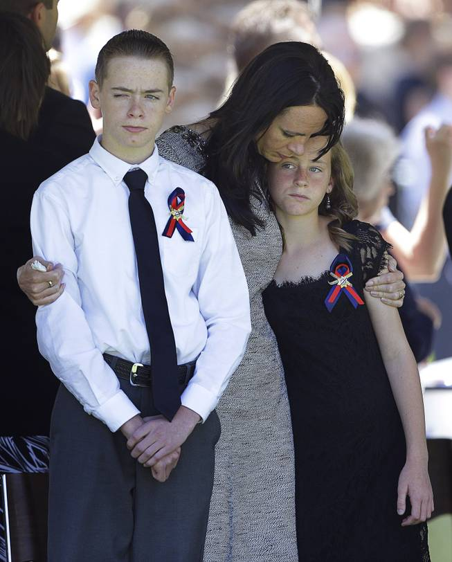 Nicole Beck, center, comforts her children Daxton Beck, left, and Avenlee Beck at a memorial for Nicole Beck's husband and the children's father Las Vegas Metropolitan Police Officer Alyn Beck at The Smith Center for the Performing Arts Saturday, June 14, 2014 in Las Vegas. Two suspects shot and killed Beck, 41, and fellow police officer Igor Soldo, 31, in an ambush at a Las Vegas restaurant Sunday, June 8, 2014, before fatally shooting a third person inside a nearby Wal-Mart, authorities said.