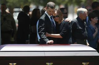 Joseph Beck, left, holds an unidentified woman as they stand over the casket of Beck's brother, Metro officer Alyn Beck during a memorial at The Smith Center for the Performing Arts Saturday, June 14, 2014.