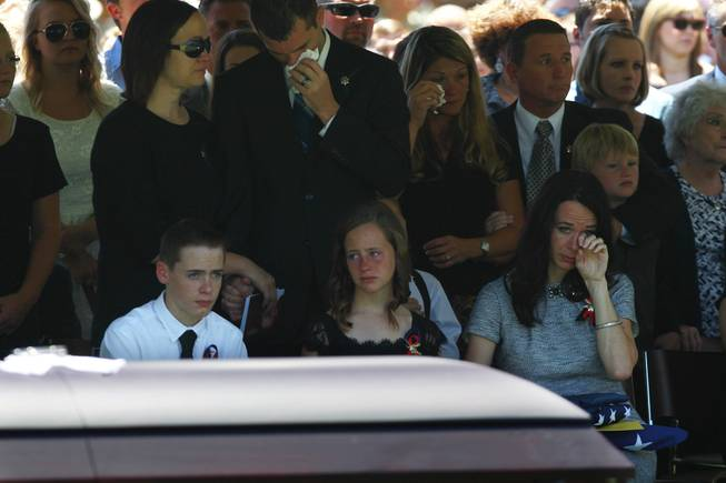 Nicole Beck wipes away a tear as she sits with son Daxton Beck, left, and Avenlee Beck during a memorial for Beck's husband and the children's father Metro officer Alyn Beck at The Smith Center for the Performing Arts Saturday, June 14, 2014.