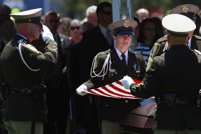 Pallbearers fold the flag from the coffin of Metro officer Alyn Beck during a memorial service Saturday, June 14, 2014 at the Smith Center for the Performing Arts.