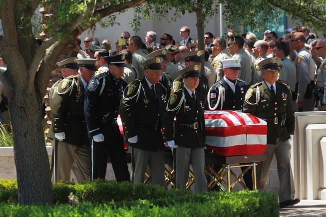 Pallbearers carry the coffin of Metro officer Alyn Beck during a memorial service Saturday, June 14, 2014 at the Smith Center for the Performing Arts.