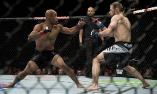Demetrious Johnson, of the United States, left, fights with Ali Bagautinov, of Russia, during the flyweight bout at UFC 174 in Vancouver, British Columbia, Saturday, June, 14, 2014.