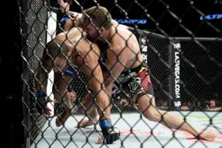 Ryan Bader, right, of the United States, puts Rafael Cavalcante, of Brazil, against the cage during a light heavyweight bout at UFC 174 in Vancouver, British Columbia, Saturday, June, 14, 2014. (AP Photo/The Canadian Press, Jonathan Hayward)