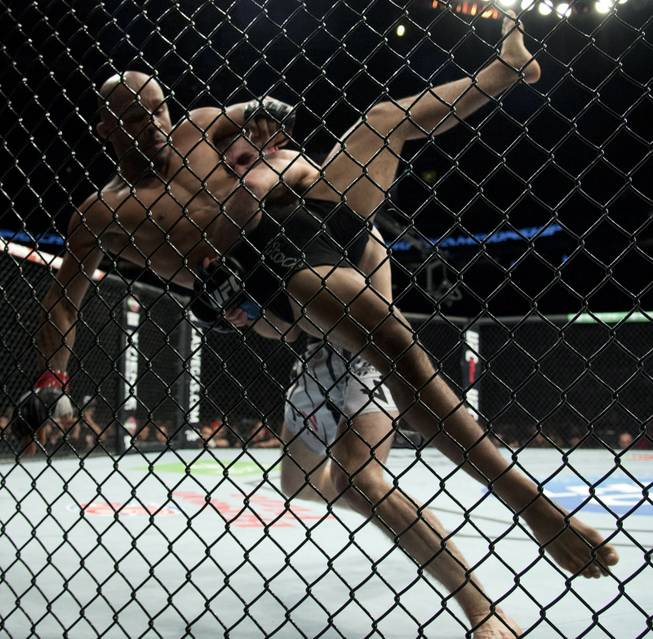 Demetrious Johnson, of the United States, left, gets thrown by Ali Bagautinov, of Russia, during the flyweight bout at UFC 174 in Vancouver, British Columbia, Saturday, June, 14, 2014.