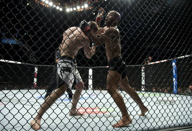 Demetrious Johnson, of the United States, right, fights Ali Bagautinov, of Russia, during the flyweight bout at UFC 174 in Vancouver, British Columbia, Saturday, June, 14, 2014.