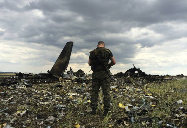 A pro-Russian fighter guards the site of remnants of a downed Ukrainian army aircraft Il-76 at the airport near Luhansk, Ukraine, on Saturday, June 14, 2014. Pro-Russian separatists shot down the military transport plane Saturday in the country's restive east, killing all 49 service personnel on board, Ukrainian officials said.
