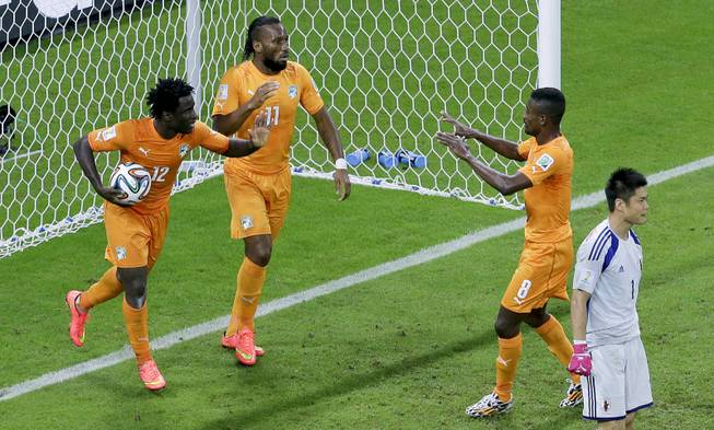 Ivory Coast's Wilfried Bony, left, celebrates with this teammates Didier Drogba, center, and Salomon Kalou, after scoring their first goal against Japan's goalkeeper Eiji Kawashima during the group C World Cup soccer match between Ivory Coast and Japan at the Arena Pernambuco in Recife, Brazil, Saturday, June 14, 2014.