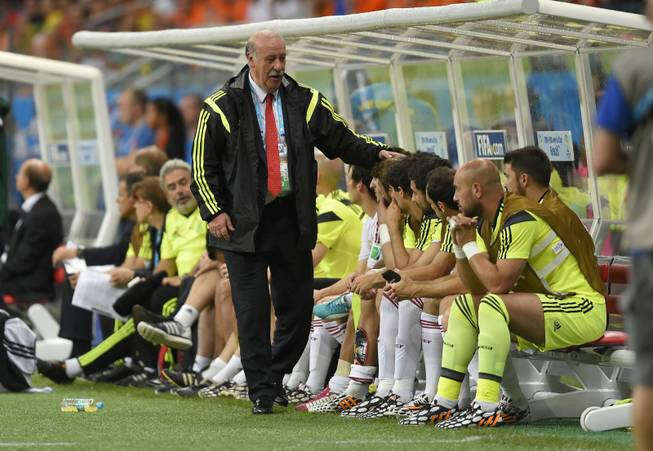 Spain's head coach Vicente Del Bosque greets his bench players during the group B World Cup soccer match between Spain and the Netherlands at the Arena Ponte Nova in Salvador, Brazil, Friday, June 13, 2014. The Netherlands won the match 5-1.