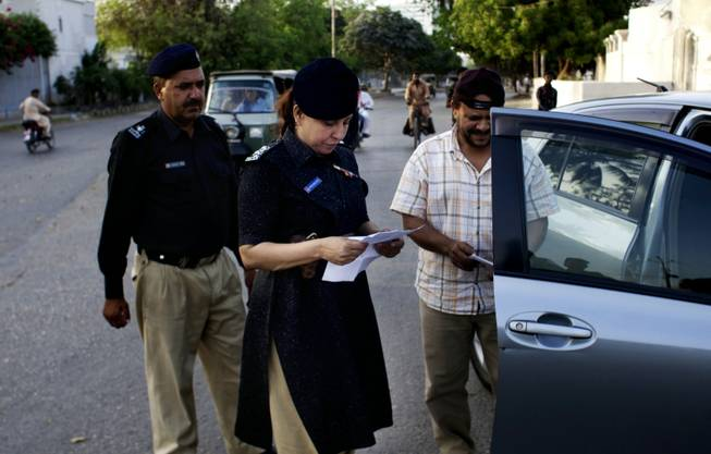 Pakistani female police officer Syeda Ghazala checks documents of a vehicle in Karachi, Pakistan. Just days into her job running a police station in Pakistan's largest city, Syeda Ghazala had to put her training to the test: she opened fire with her .22-caliber pistol at a man who shot at police when they tried to pull him over during a routine traffic stop.