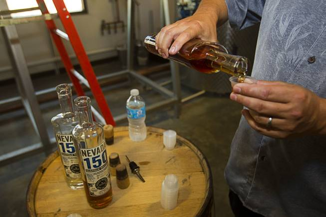 "Mike Derby pours samples of ""Nevada 150"" bourbon whiskey during ""Bourbon Day"" at the Las Vegas Distillery in Henderson Saturday, June 14, 2014. The bourbon, the first bourbon produced in Nevada, is named for Nevada's sesquicentennial."