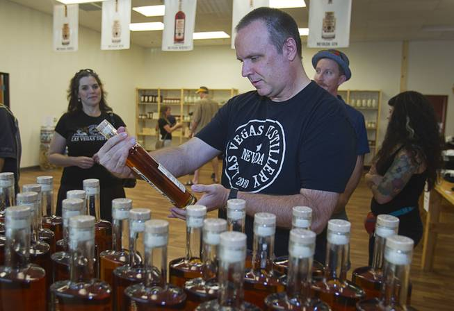 "Paul Norman, vice president of Schmooze Brothers Distribution, looks over a bottle of ""Nevada 150"" bourbon whiskey during ""Bourbon Day"" at the Las Vegas Distillery in Henderson Saturday, June 14, 2014. The bourbon, the first bourbon produced in Nevada, is named for Nevada's sesquicentennial."