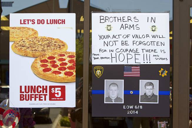 "Photos of Metro Police Officers Igor Soldo, left, and Alyn Beck are shown at a memorial during ""Sharing Our Support,"" a fundraiser for the officer's families, at CiCi's Pizza Sunday, June 15, 2014. The officers were ambushed and killed at the restaurant while eating lunch on Sunday, June 8. One hundred percent of the Sunday sales will go the families of the fallen officers and Joseph Willcox, the victim killed at the Wal-Mart, said store owner Mike Haskins."