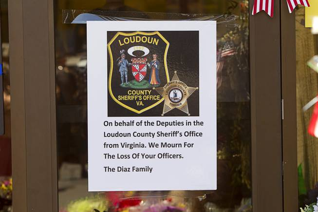 "A sign from the Loudoun County Sheriff's office in Virginia is posted at a memorial during ""Sharing Our Support,"" a fundraiser for the families of Metro Police Officers Igor Soldo and Alyn Beck, at CiCi's Pizza Sunday, June 15, 2014. The officers were ambushed and killed at the restaurant while eating lunch on Sunday, June 8. One hundred percent of the Sunday sales will go the families of the fallen officers and Joseph Willcox, the victim killed at the Wal-Mart, said store owner Mike Haskins."