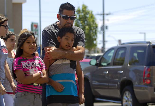 "Ricardo Vazquez and his children Mireya, left, and Richardo Jr., look over a memorial during ""Sharing Our Support,"" a fundraiser for the families of Metro Police Officers Igor Soldo and Alyn Beck, at CiCi's Pizza Sunday, June 15, 2014. The officers were ambushed and killed at the restaurant while eating lunch on Sunday, June 8. One hundred percent of the Sunday sales will go the families of the fallen officers and Joseph Willcox, the victim killed at the Wal-Mart, said store owner Mike Haskins."
