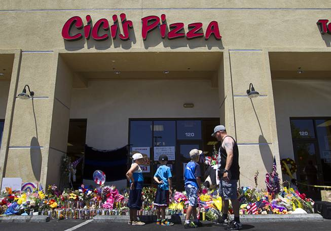 "Jarod Gaskins and his sons look over a memorial during ""Sharing Our Support,"" a fundraiser for the families of Metro Police Officers Igor Soldo and Alyn Beck, at CiCi's Pizza Sunday, June 15, 2014. The officers were ambushed and killed at the restaurant while eating lunch on Sunday, June 8. One hundred percent of the Sunday sales will go the families of the fallen officers and Joseph Willcox, the victim killed at the Wal-Mart, said store owner Mike Haskins."