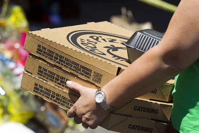 "A customer carries out pizza-to-go during ""Sharing Our Support,"" a fundraiser for the families of Metro Police Officers Igor Soldo and Alyn Beck, at CiCi's Pizza Sunday, June 15, 2014. The officers were ambushed and killed at the restaurant while eating lunch on Sunday, June 8. One hundred percent of the Sunday sales will go the families of the fallen officers and Joseph Willcox, the victim killed at the Wal-Mart, said store owner Mike Haskins."