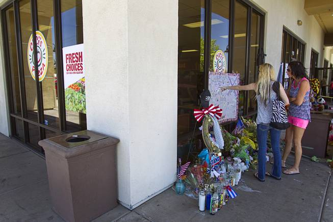 "Katie Lynn Coffin, center, and Tanya Akers of Pahrump look over a memorial during ""Sharing Our Support,"" a fundraiser for the families of Metro Police Officers Igor Soldo and Alyn Beck, at CiCi's Pizza Sunday, June 15, 2014. The officers were ambushed and killed at the restaurant while eating lunch on Sunday, June 8. One hundred percent of the Sunday sales will go the families of the fallen officers and Joseph Willcox, the victim killed at the Wal-Mart, said store owner Mike Haskins."