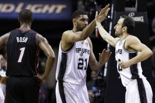 San Antonio Spurs forward Tim Duncan (21) and guard Manu Ginobili celebrate as Miami Heat center Chris Bosh (1) walks away during the first half in Game 5 of the NBA basketball finals on Sunday, June 15, 2014, in San Antonio.