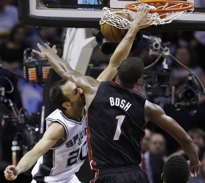 San Antonio Spurs guard Manu Ginobili (20) dunks as Miami Heat center Chris Bosh (1) defends during the first half in Game 5 of the NBA basketball finals on Sunday, June 15, 2014, in San Antonio.