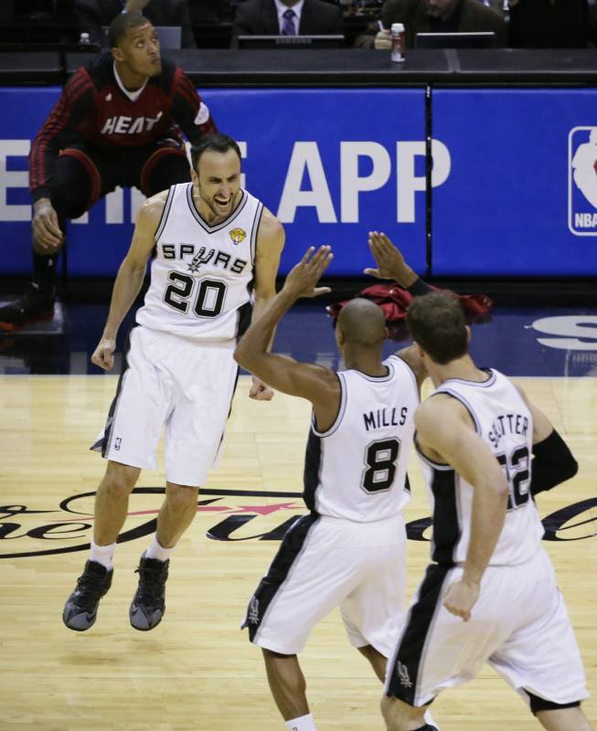 San Antonio Spurs guard Manu Ginobili (20), guard Patty Mills (8) and center Tiago Splitter (22) celebrate against the Miami Heat during the second half in Game 5 of the NBA basketball finals on Sunday, June 15, 2014, in San Antonio. (AP Photo/