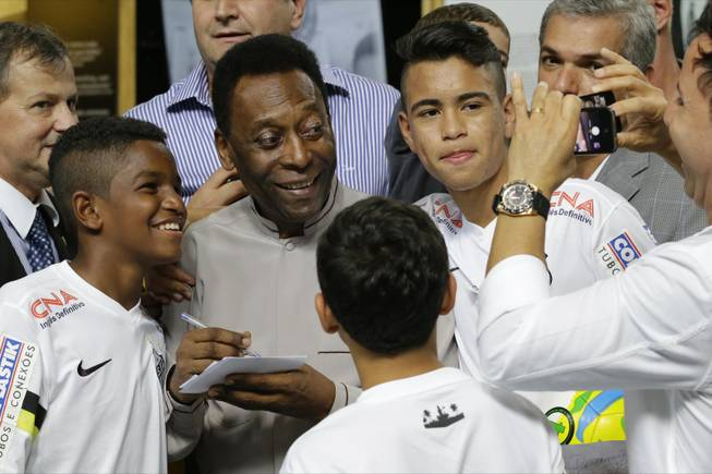 Soccer great Pele pose for a photo next to young players of the Santos soccer team during the inauguration of the Pele Museum in Santos, Brazil, Sunday, June 15, 2014. The Pele Museum exhibits his personal collection, pictures, films, trophies and printed material about his history as a soccer player and personality.