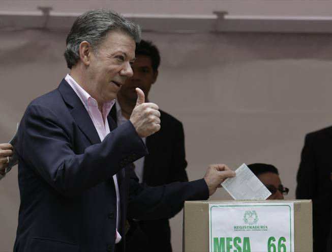 President Juan Manuel Santos casts his ballot during presidential elections in Bogota, Colombia, Sunday, June 15, 2014. Santos won a second four-year term as candidate for the Social Party of National Unity.