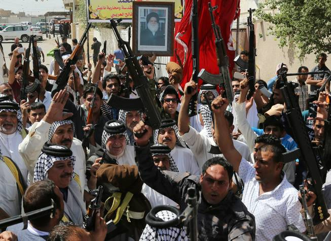 In this Saturday, June 14, 2014, photo, Iraqi Shiite tribal fighters raise their weapons and chant slogans against the al-Qaida-inspired Islamic State of Iraq and the Levant (ISIL) in Baghdad's Sadr city, Iraq. Emboldened by a call to arms by the top Shiite cleric, Iranian-backed militias have moved quickly to the center of Iraq's political landscape, spearheading what its Shiite majority sees as a fight for survival against Sunni militants who control of large swaths of territory north of Baghdad. The poster at top depicts Grand Ayatollah Mohammed Sadiq al-Sadr, the late father of Shiite cleric Muqtada al-Sadr.