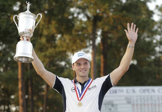 Martin Kaymer of Germany holds up the trophy after wining the U.S. Open golf tournament in Pinehurst, N.C., Sunday, June 15, 2014.