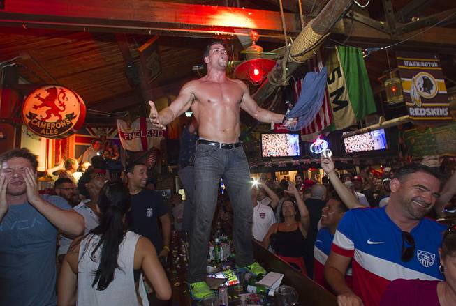 A soccer fan celebrates on a bar after watching the United States beat Ghana 2-1 in the World Cup during a viewing party at the Crown & Anchor British Pub Monday, June 16, 2014.