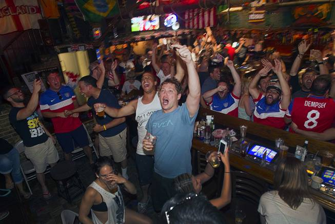 Joel Tonkel, center, and other soccer fans celebrate as they watch the United States make their first goal against Ghana in the World Cup during a viewing party at the Crown & Anchor British Pub Monday, June 16, 2014.