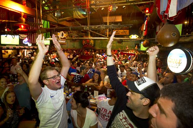 Aaron Kemper, left,  and other soccer fans celebrate after the United States makes their first goal against Ghana in the World Cup during a viewing party at the Crown & Anchor British Pub Monday, June 16, 2014.