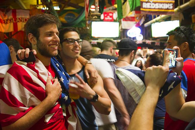 Ian Weinberg, left,  poses with a friend at halftime during a viewing party at the Crown & Anchor British Pub Monday, June 16, 2014.