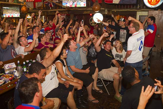 Aaron Kemper, right, leads fans in a chant as they watch the United States beat Ghana 2-1 in the World Cup during a viewing party at the Crown & Anchor British Pub Monday, June 16, 2014.