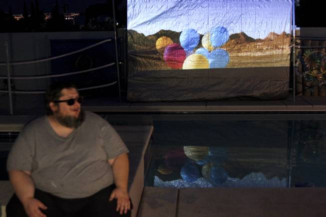 Scott Grow talks about his work while a video of his performance plays in the background during the 2014 London Biennale in Las Vegas, a satellite site for the biennale, Saturday, June 14, 2014.