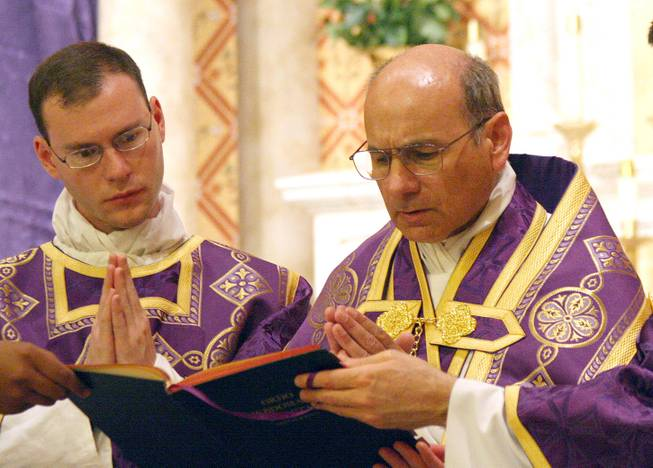 In this photo provided by The Catholic Sun, date not known, the Rev. Kenneth Walker, left, and the Rev. Joseph Terra perform a Mass in Phoenix. Walker was killed and Terra was critically injured during a robbery attempt at Mater Misericordiae Mission on Wednesday, June 11, 2014.