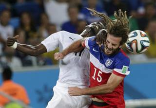 Ghana's Mohammed Rabiu, left, and United States' Kyle Beckerman struggle with each other to head the ball during the group G World Cup soccer match between Ghana and the United States at the Arena das Dunas in Natal, Brazil, Monday, June 16, 2014.  (AP Photo/Petr David Josek)