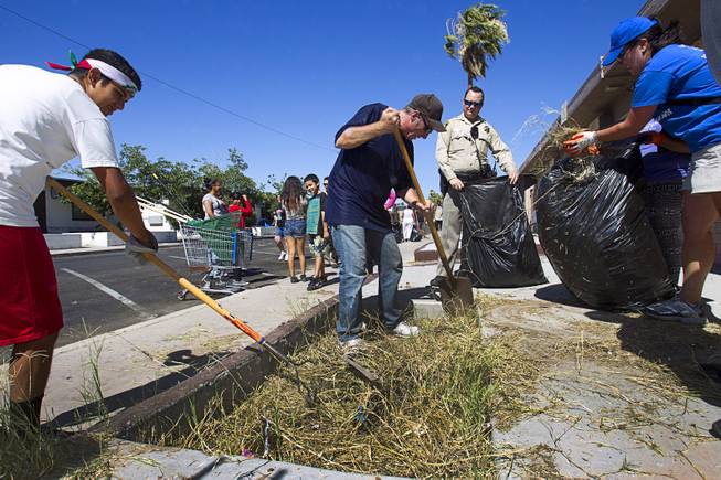 Resident Claudio Solis, 16, left, Carl Thompson, center, and Downtown Dynamo Sarah Ning participate in a Downtown Community Coalition neighborhood cleanup near Fremont Street and 21st Street Tuesday, June 17, 2014. An estimated 8 tons of garbage was collected during the event, said Metro Police Officer Aden Ocampo-Gomez. A bobcat from the city's rapid response unit picked up the larger items such as an abandoned couch and discarded mattresses, he said.