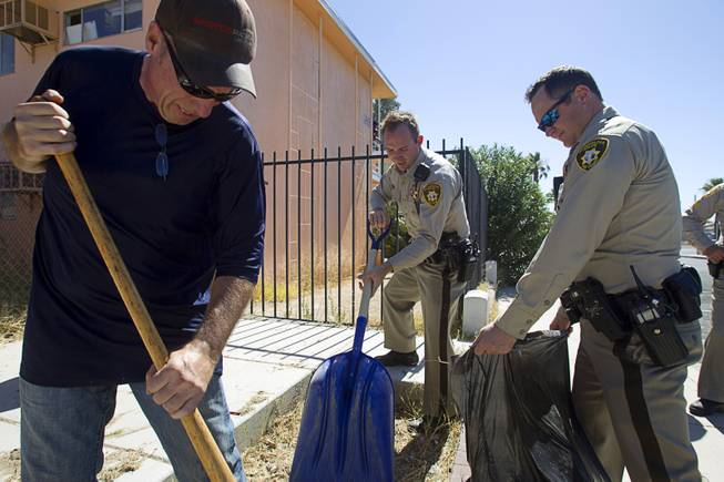 Carl Thompson, left, and Metro Police officers participate in a Downtown Community Coalition neighborhood cleanup near Fremont Street and 21st Street Tuesday, June 17, 2014. A variety of community, church and business groups, along with Metro Police and the City of Las Vegas, participated in the event.