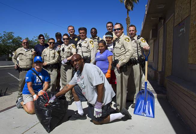 Metro Police officers pose with residents and volunteers during a Downtown Community Coalition neighborhood cleanup near Fremont Street and 21st Street Tuesday, June 17, 2014. A variety of community, church and business groups, along with Metro Police and the City of Las Vegas, participated in the event.
