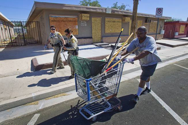 Arthur Jennings pushes a shopping cart with rakes and brooms during a Downtown Community Coalition neighborhood cleanup near Fremont Street and 21st Street Tuesday, June 17, 2014. A variety of community, church and business groups, along with Metro Police and the City of Las Vegas, participated in the event.