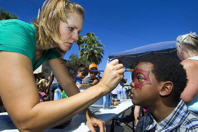 Margaret Nitzel of Verve Church paints the face of Samajay Bright, 8, during a Downtown Community Coalition neighborhood cleanup near Fremont Street and 21st Street Tuesday, June 17, 2014. A variety of community, church and business groups, along with Metro Police and the City of Las Vegas, participated in the event.