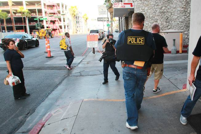 Undercover Metro officers carry away evidence from the office of Las Vegas Township Constable John Bonaventura Tuesday, June 17, 2014. Detectives were searching for evidence of illegal use of a listening device.